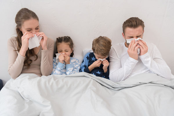 Sick parents ans children lying in a bed and blowing noses in napkins