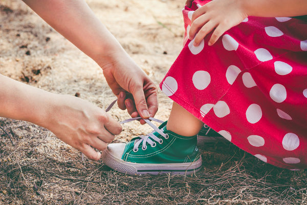 mother-helping-daughter-to-tie-shoes