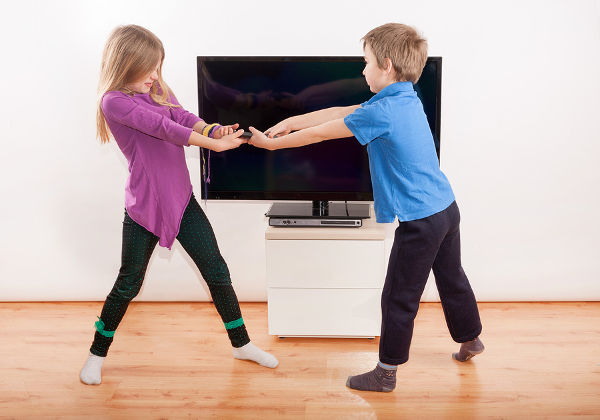 Sibling fighting over the remote controll in front of the TV