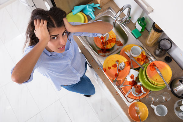 Frustrated Young Woman Standing Near Messy Utensils On Countertop In Kitchen