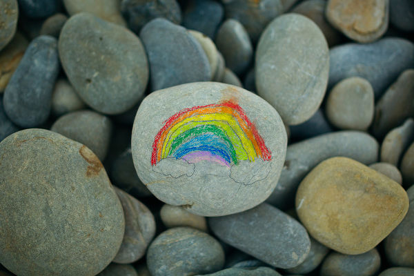 Close-up of painted rainbow on stone on pebble beach.