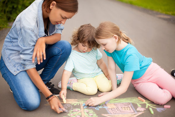 Little girls chalking at the asphalt with elder sister or nanny. Sisters friendship. Best friends children happy family. Drawing with color chalk. Happy childhood. Kids in kindergarten. Preschooler leisure time. Kids spending time without parents. Childre