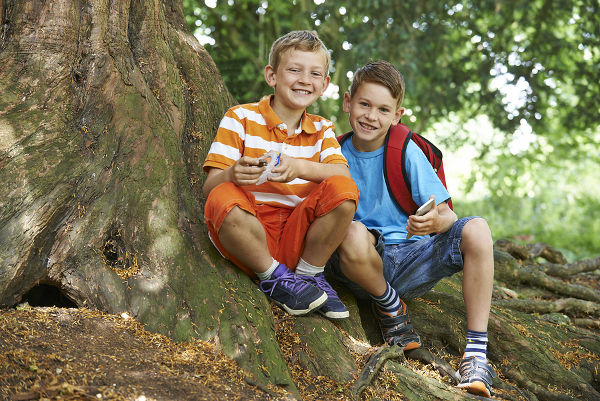 Portrait Of Two Boys Geocaching In Woodland
