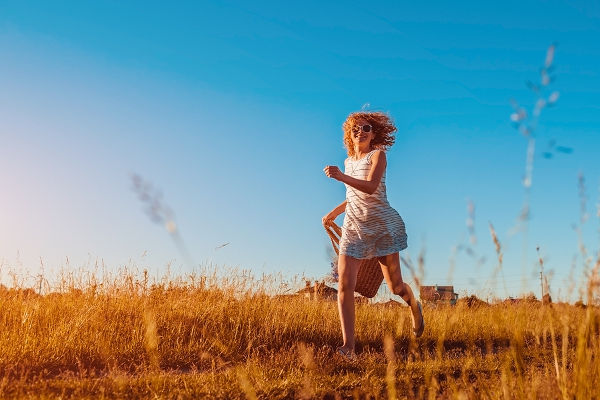 fashionable-woman-running-through-field