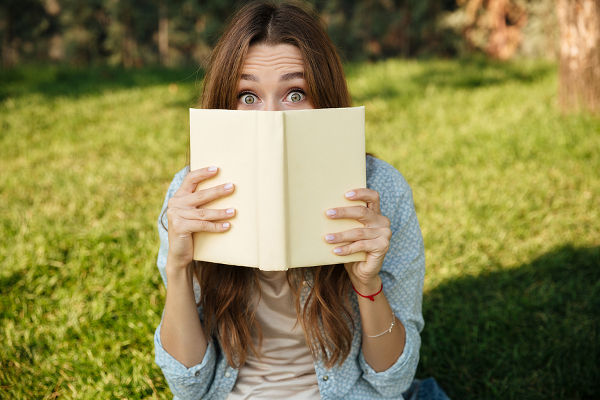 Young brunette woman sitting in park and hiding behind a book