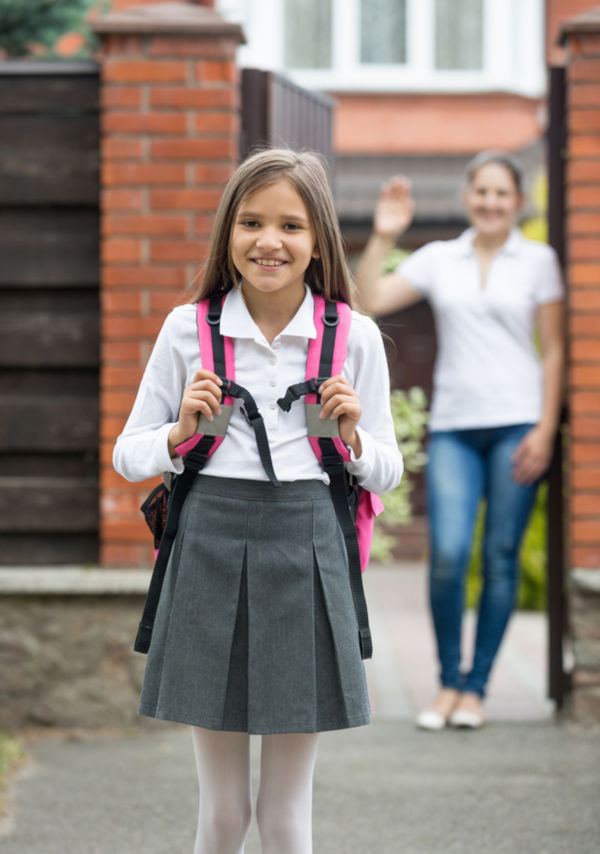 Smiling girl with school bag standing at house gates