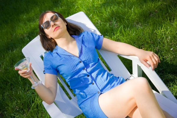 Woman lying on the sun lounger with a glass of martini