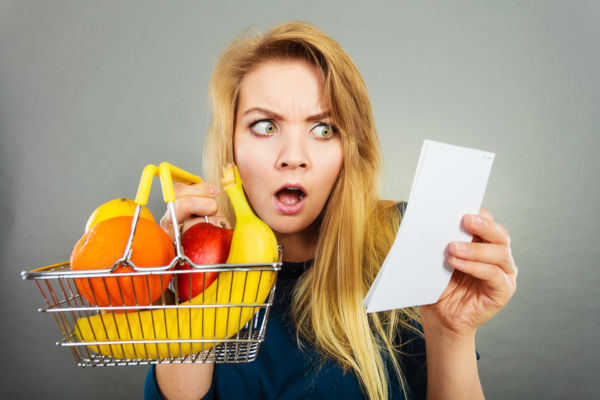 Shocked Woman Holding Shopping Basket With Fruits Looking At Bil