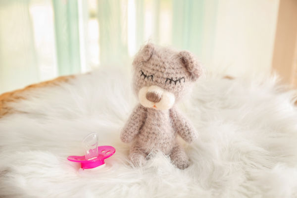 Cute baby toy and pacifier on fluffy plaid