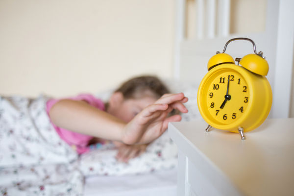 school child sleeps in bed. yellow alarm clock on nightstand in background of bed and sleeping kid in interior of room.