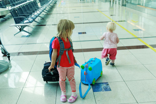 kids with suitcase travel in the airport, family travel