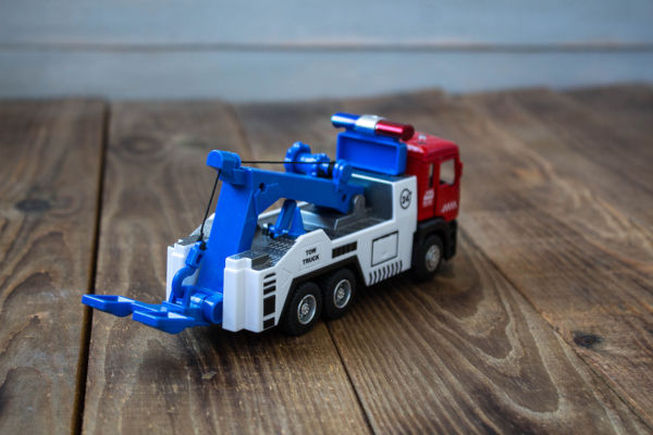 a tow truck childrens toys on wooden background