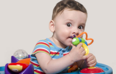 Cute baby boy sitting and playing with toys. Adorable six month old child chewing a toy. Baby teething.