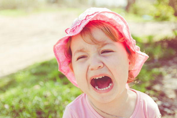 Portrait of an unhappy child. Baby screams. The child is angry