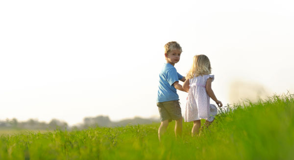 Brother and sister playing together in a field