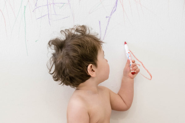cute little baby boy drawing with crayon color on the wall. Works of child. Works of child. Caucasian brunette child 1 year old