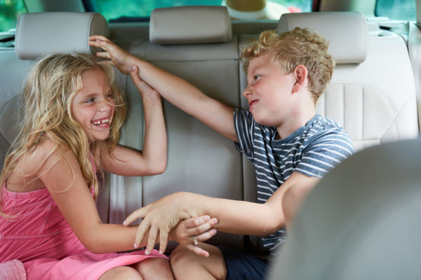 Two children are fighting and arguing with each other in the car