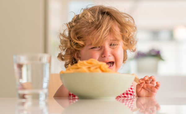 Beautiful blond child eating spaghetti with hands crying with ta