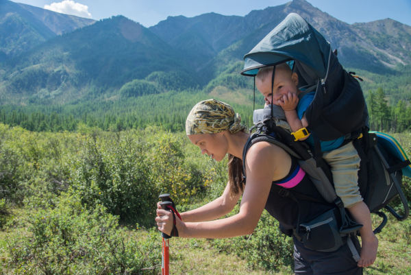 Tired Woman Hiker Trekking In Mountains With Child In Backpack,