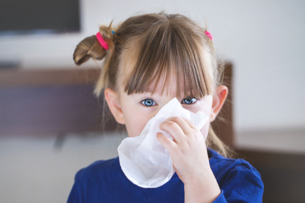 Child blows her nose into a handkerchief.
