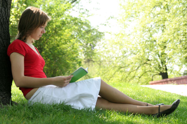 Portrait of a young woman reading book in the park