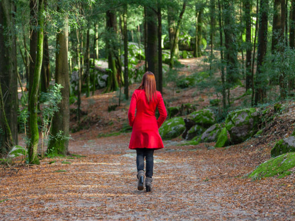 Young woman walking away alone on forest path wearing red long coat or overcoat.