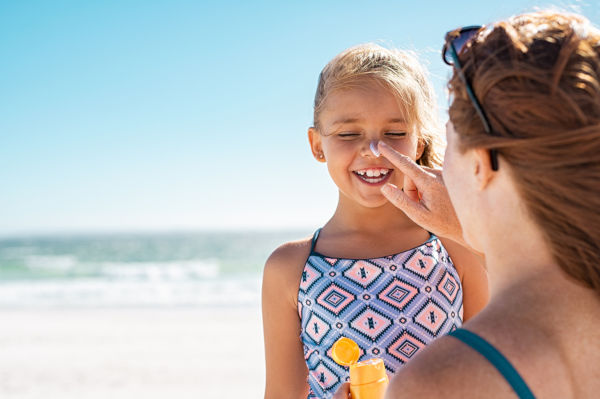 Young mother applying protective sunscreen on daughter nose at beach