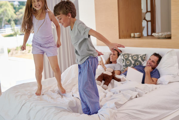 boy and girl siblings jumping on parents bed