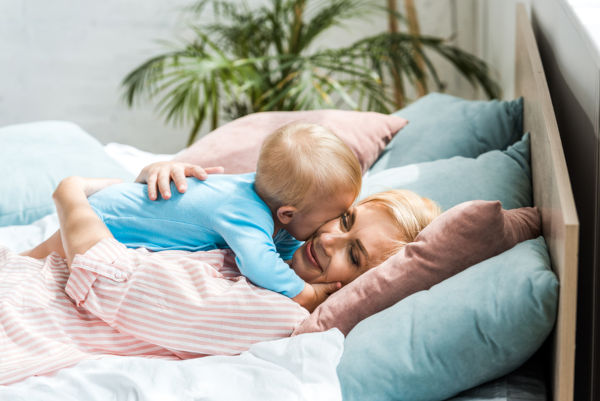 Mother Hugging Cute Toddler Son While Lying On Bed