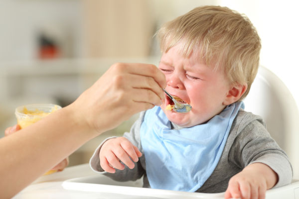 Toddler sitting in high chair and crying about food he is being fed