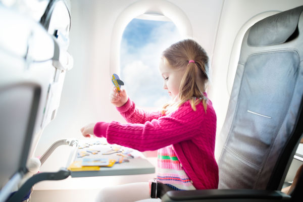 Young girl sat in aeroplane