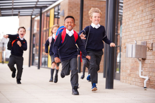 Primary school children in uniform running at school
