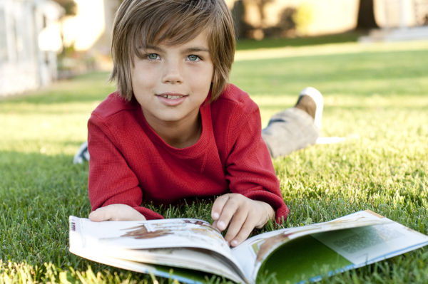 Boy lying on grass reading a book