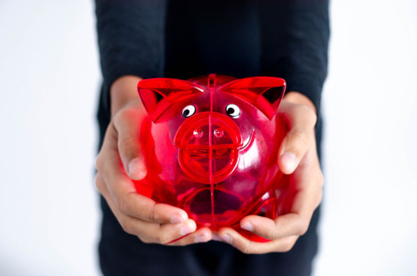 Red pig money box held in a woman's hands