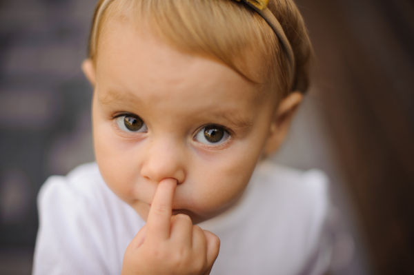 Cute little baby girl picking her nose close up
