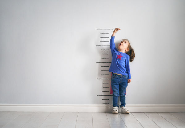 Child dressed as a superhero measuring herself on a height chart