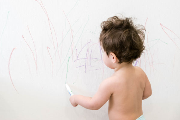 toddler drawing on the wall with lots of scribbles