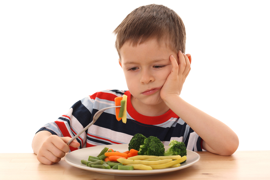Boy with a plate of vegetables that he doesn't like