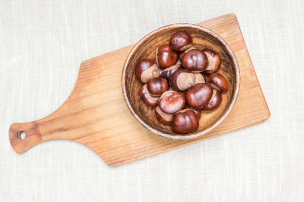 Conkers on chopping board, from a horse chestnut tree