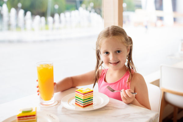 Girl eating a rainbow cake in a cafe