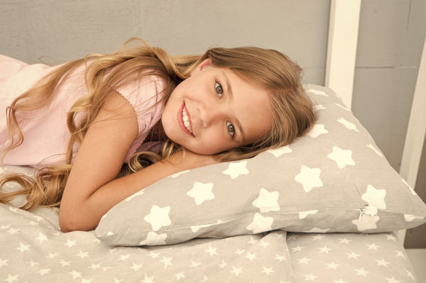 Young girl lying on her bed with a pillow