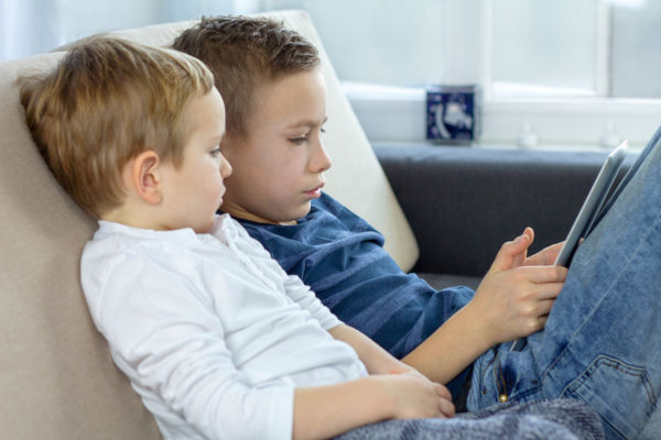 Two Kids Using Touchscreen Tablet At Home,