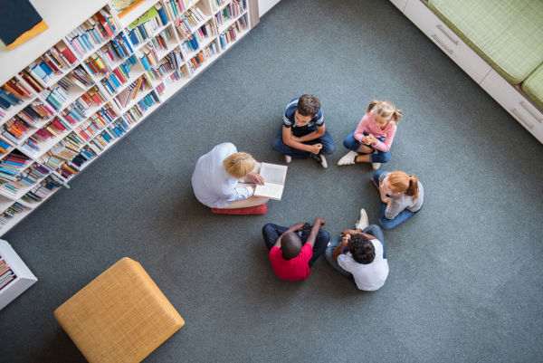 Librarian reading to children sat in a circle in library
