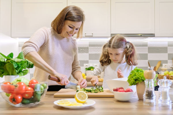 Mother And Child Cooking Together At Home In Kitchen.