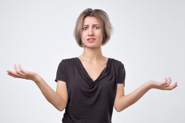 Woman shrugging, looking confused
