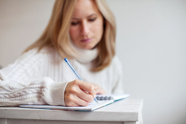 Woman writing pen in notebook. Female writing letter