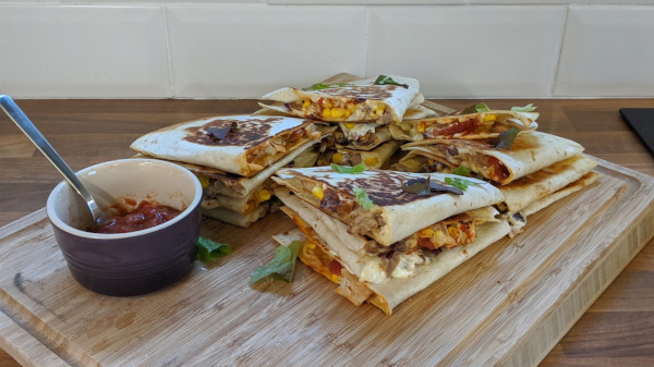 Piles of Quesadillas on a chopping board with salsa