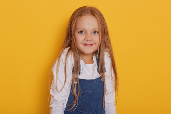Smiling little girl on a yellow background