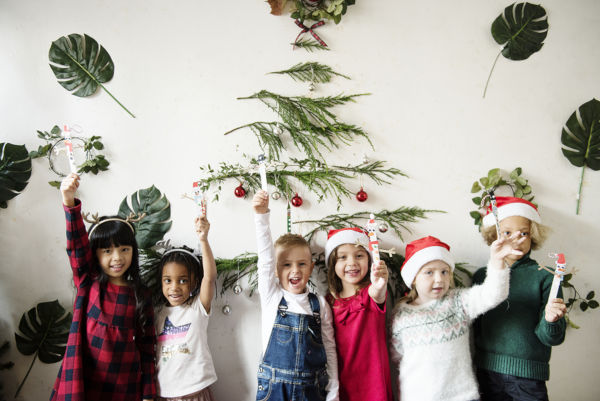 Group of children in Christmas hats by a Christmas tree