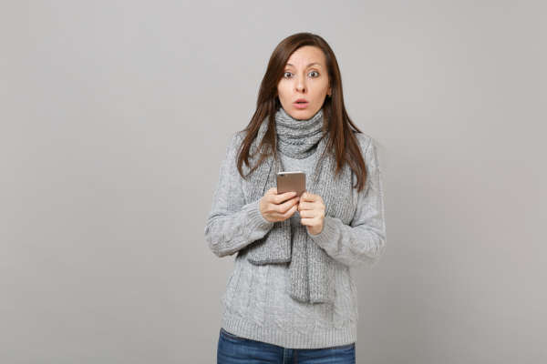 Woman in grey scarf looking surprised at phone messages